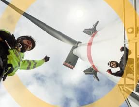 men working under a wind turbine