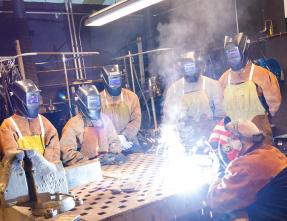 students and instructor in a welding lab